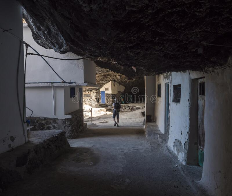 Tourist man at Cueva de Candelaria, Pirate cave Poris de Candelaria, small fisherman village hidden under rock cornice. With white blue houses, attraction near stock photography