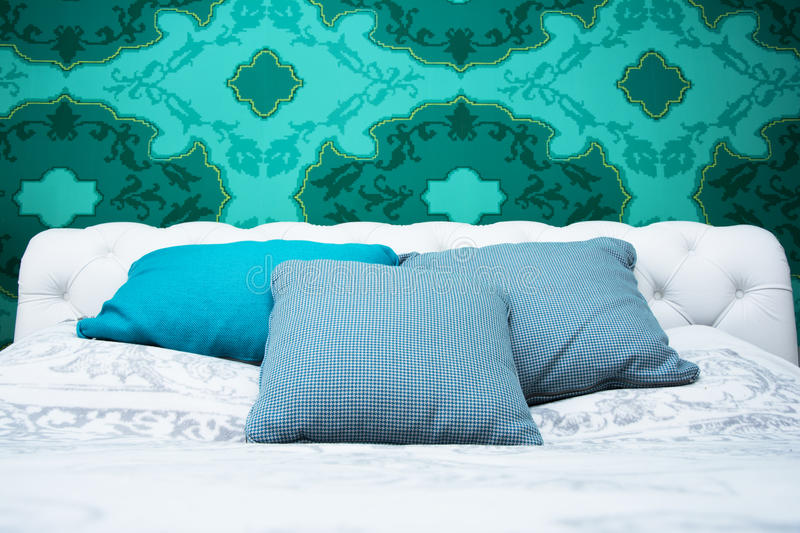 Turquoise blue and white bedroom. Bedroom design with colorful wallpaper and turquoise and white color royalty free stock images