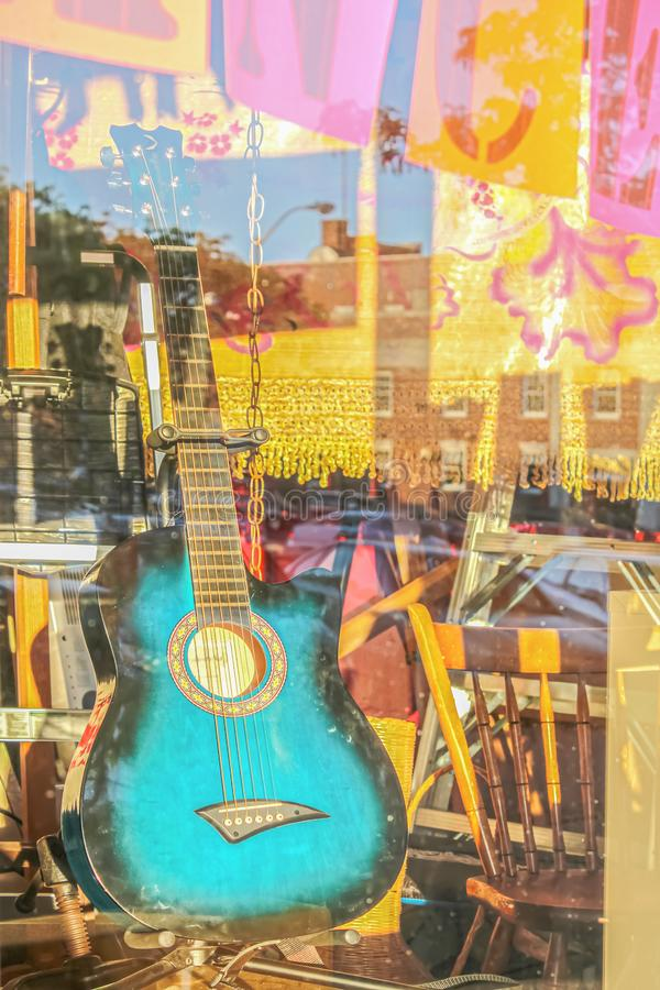Turquoise decorated guitar propped up in shop window with reflections and pink and yellow boho hangings behind.  royalty free stock image