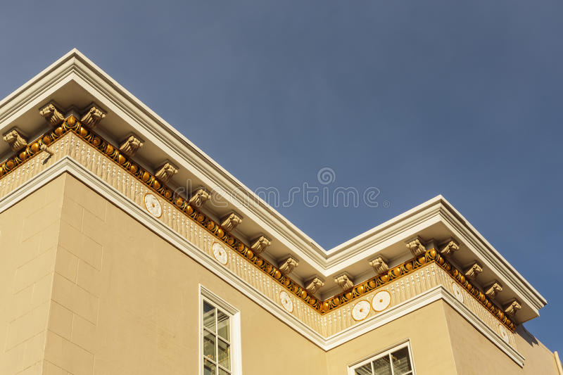 Upscale house roof and cornice detail. Detail of the roof and cornice of an upscale modern home against a blue sky stock photography