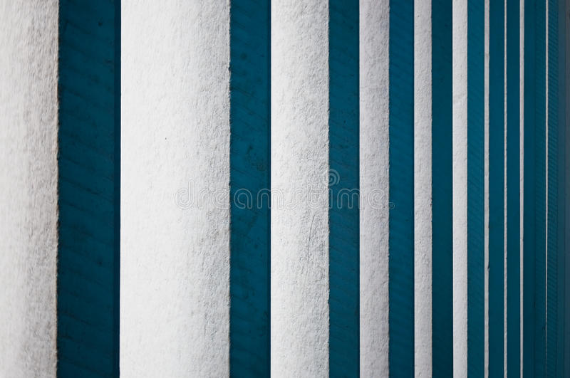 Vertical white wooden blinds. Abstract background. Vertical fixed wooden blinds painted in white appear in blue shade by the ambient blue light from the roof stock images