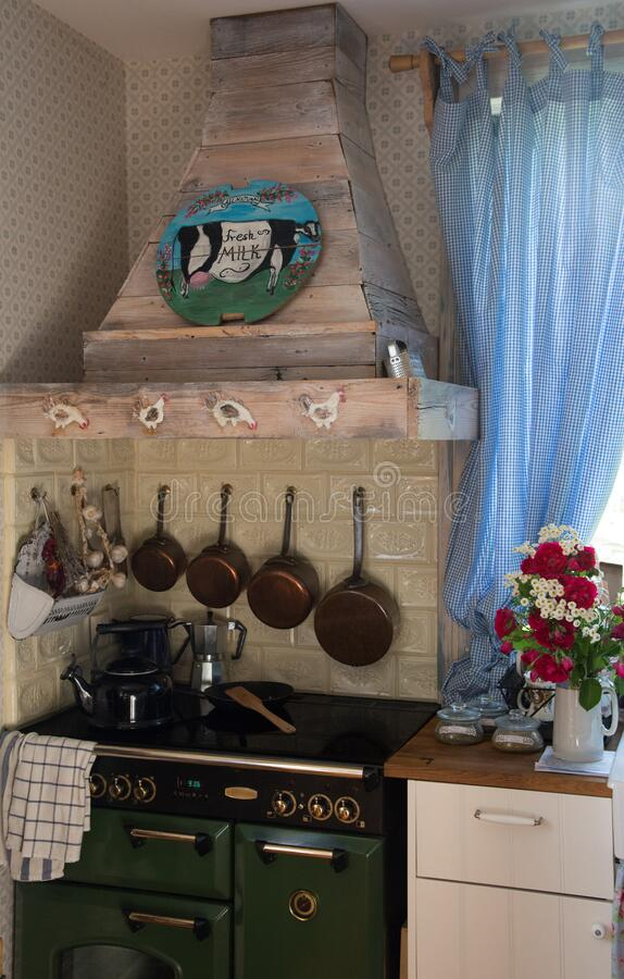 Vintage english kitchen from Poland. Kitchen with wooden hood, english stove, hand made piece of art, french saucepans hanging on the tiled wall. Fresh flowers stock photo