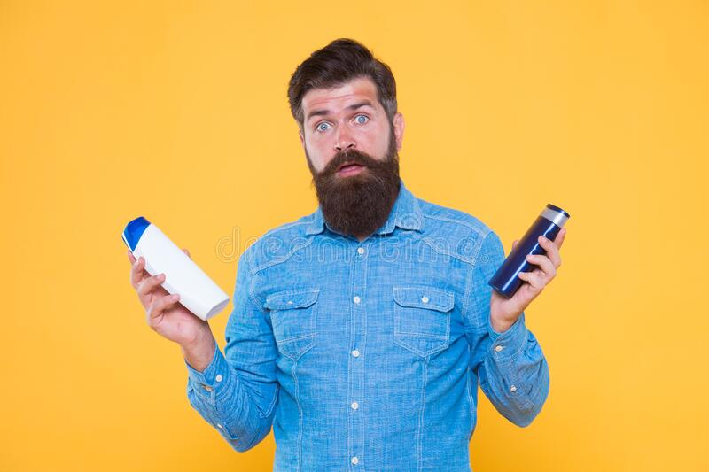 Which soap best. Bearded man hold soap bottles yellow background. Hipster choose liquid soap. For washing in bath or. Shower. Skincare and health. Grooming and stock photo