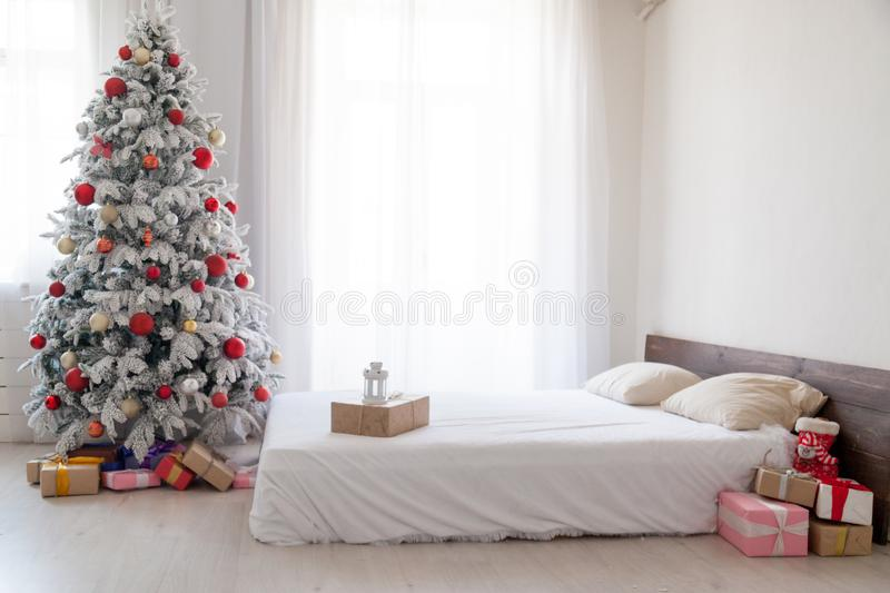 White Christmas tree with red bedroom toys new year winter gifts decor. White Christmas tree with red bedroom toys new year winter gifts royalty free stock photography