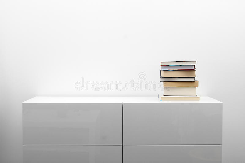 White commode with stack of books in bright minimalism interior. White commode with stack of books in minimalism interior stock image