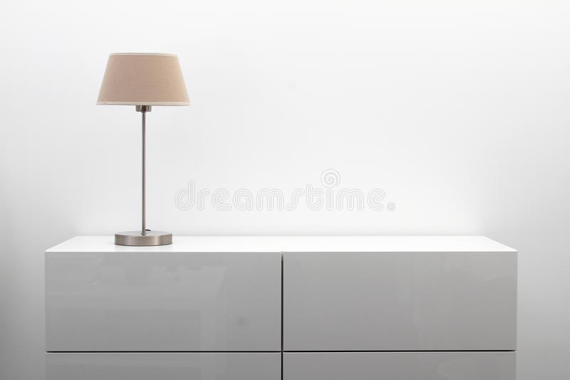 White commode with table lamp in bright minimalism interior. White commode with table lamp in bright modern minimalism interior royalty free stock photos