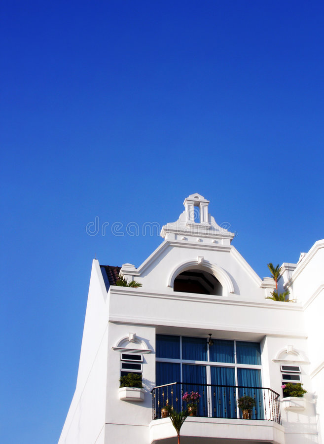 White house, blue tropical sky. A beautiful new house in white, with a balcony and a quaint cupola on top, taken under an azure blue tropical sky in the bright royalty free stock photo
