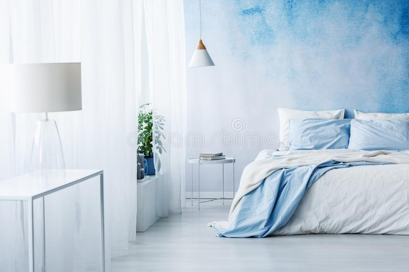 White lamp on a table in bright blue bedroom interior with bed a. Gainst ombre wall royalty free stock image