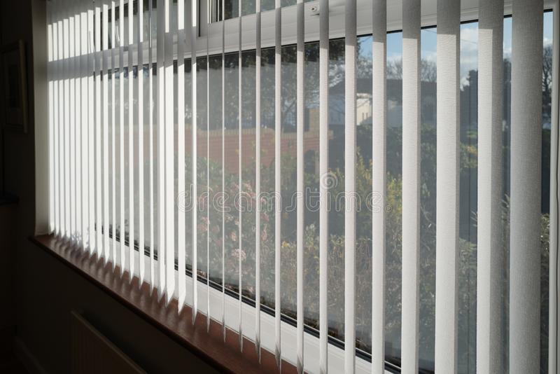 White vertical blinds slats hanging in front of double glazed white frame window. The slats have no cords at the bottom. The focus is shallow stock photos