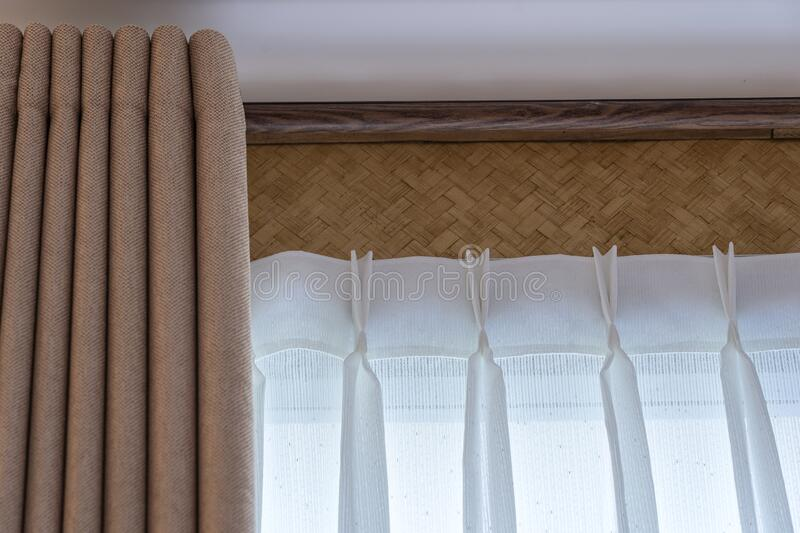 Window beige curtains and white tulle on the curtain rod. Close up royalty free stock photos