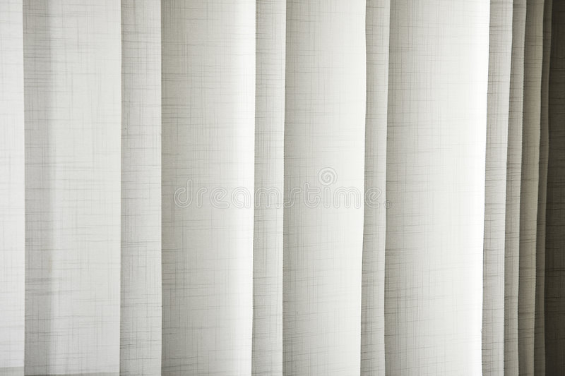 Window blinds. Vertical textile window blinds - jalousie in shades of light brown and grey, stripes background stock images