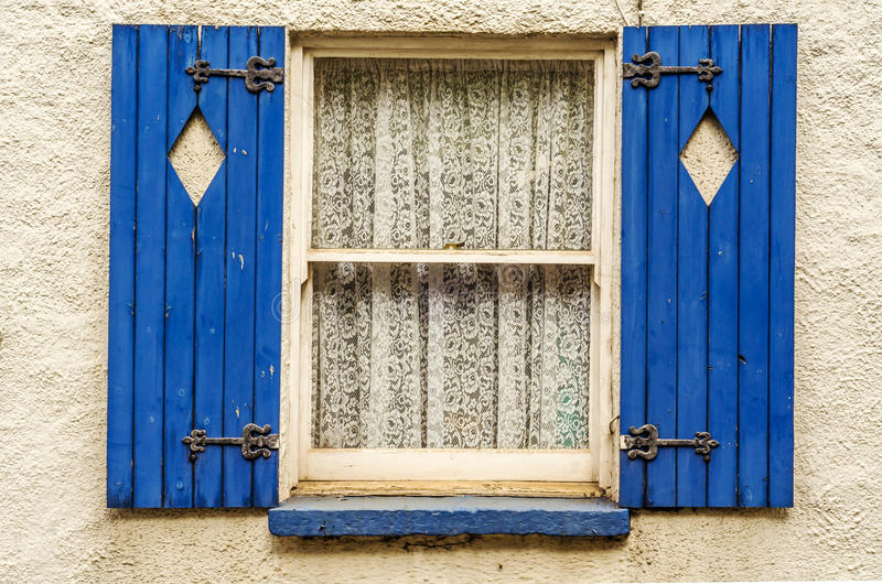 Window with wooden shutters, diamond shape cut in shutters, shut. Ters painted in blue, beautiful patterned curtains, architecture royalty free stock image