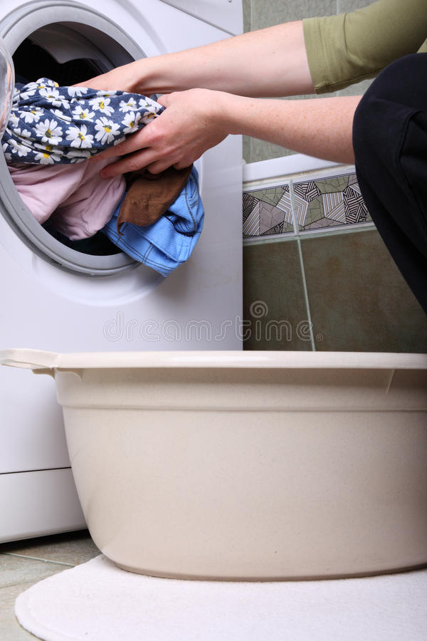 Woman loading the washing machine in bathroom stock photos