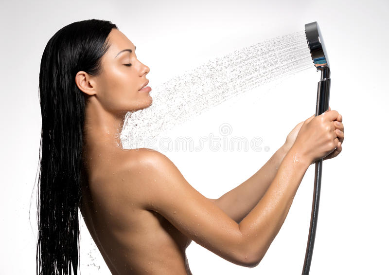 Woman in shower washing body under the stream of water. Photo of a beautiful woman in shower washing body under the stream of water stock photography