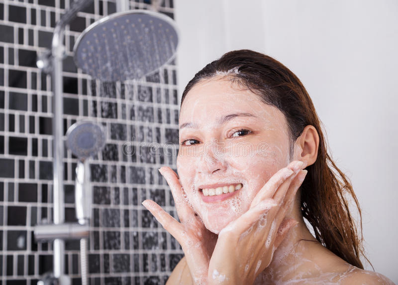 Woman washing face in shower foaming. In the bathroom royalty free stock photography