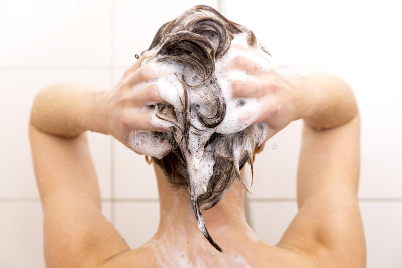 Woman washing her hair in shower. With a shampoo and by hands stock images