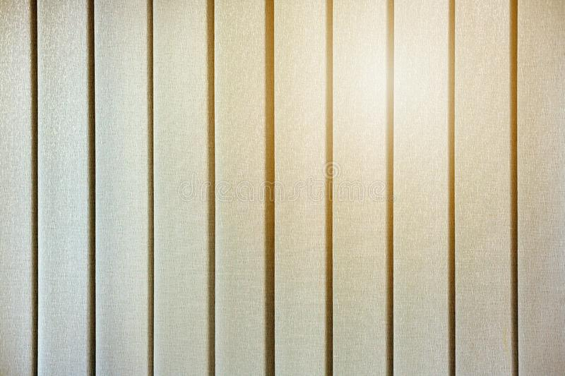The yellow glow of the sun through the closed vertical blinds on the windows.  royalty free stock photography