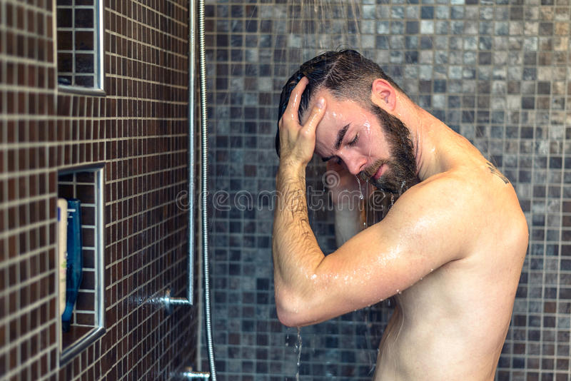 Young man washing his hair in the shower. Young man with a beard standing washing his hair in the shower with shampoo rinsing it off under the jet of water stock photos