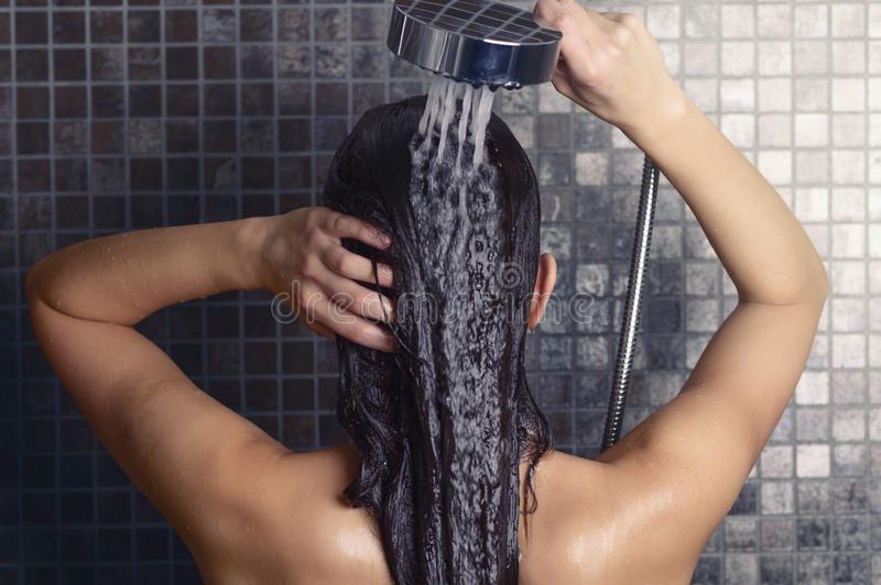 Young woman washing her long hair under the shower. Standing with her back to the camera rinsing it off under the jet of water with her head partially turned to stock photography